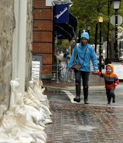 A woman and little boy enter a Starbucks fortified with sandbags in Alexandria, Virginia October 2, 2015. Powerful Hurricane Joaquin, which battered the Bahamas with torrential rain, powerful wind ...