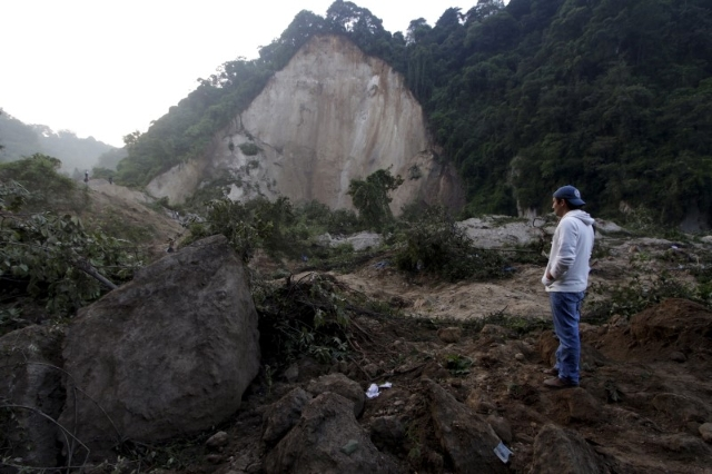 A resident looks at a landslide that destroyed his home in Santa Catarina Pinula, on the outskirts of Guatemala City, October 2, 2015.  REUTERS/Josue Decavele