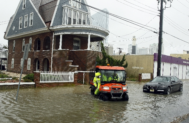 Employees drive across a street with rising flood waters, after checking a house for occupants on the north end of Atlantic Avenue city, New Jersey, October 2, 2015. Powerful Hurricane Joaquin, wh ...