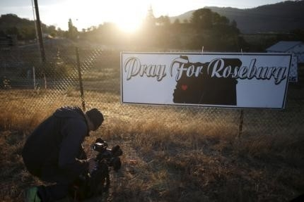 A television cameraman films a sympathy sign at sunrise outside Umpqua Community College in Roseburg, Oregon, United States, October 2, 2015.  REUTERS/Lucy Nicholson