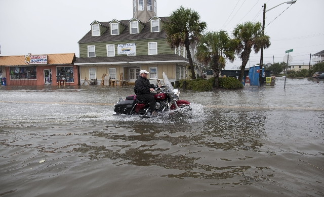 A motorcyclist navigates through flood waters in Garden City Beach, South Carolina, October 2, 2015. Category 4 Hurricane Joaquin is now moving northward and has started bringing swells to parts o ...