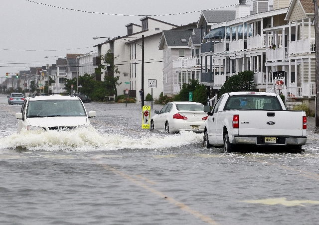 Vehicles drive along a flooded West Avenue as a nor-easter comes on shore in Ocean City, New Jersey, October 2, 2015. Hurricane Joaquin was not expected to be a major threat to the U.S. East Coast ...