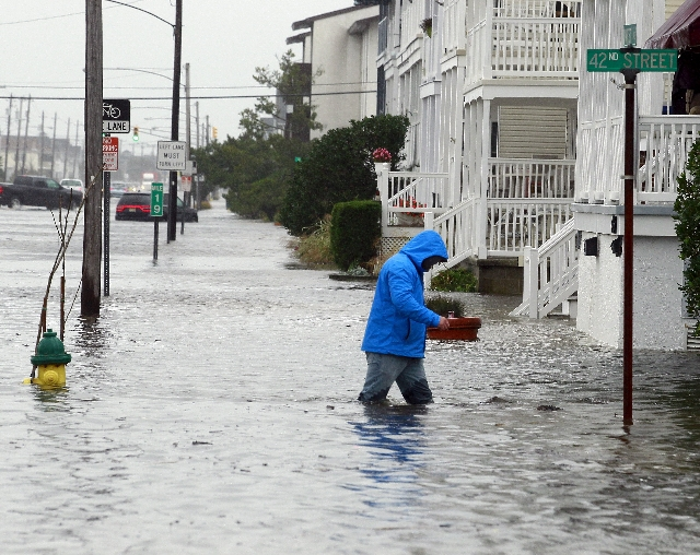 A man walks through knee-deep water along a flooded West Avenue as a nor-easter comes on shore in Ocean City, New Jersey, October 2, 2015. Hurricane Joaquin was not expected to be a major threat t ...
