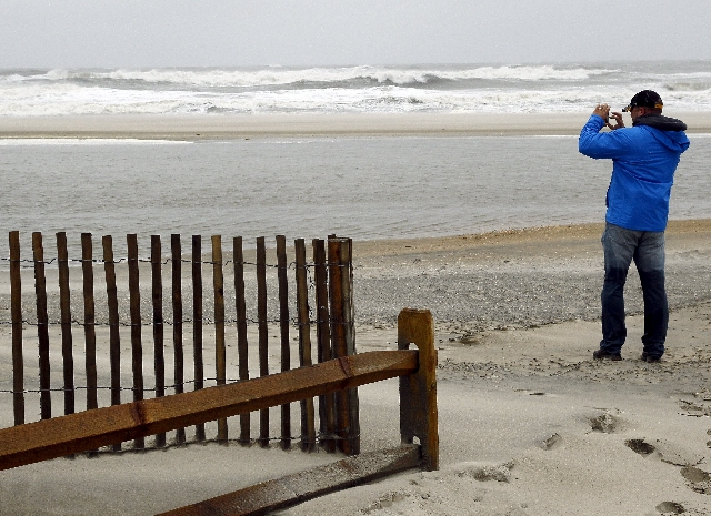 A visit to the beach takes photographs of the storm surf with his cellphone camera as a nor-easter comes on shore in Ocean City, New Jersey, October 2, 2015. Hurricane Joaquin was not expected to  ...