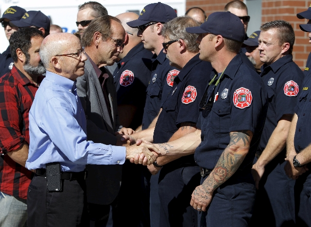 U.S. Congressman Peter DeFazio (L) shakes hands with first responders at a news conference in Roseburg, Oregon October 2, 2015. Chris Harper-Mercer, the man killed by police on Thursday after he f ...