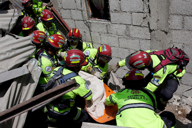 Rescue team members retrieve the body of a mudslide victim in Santa Catarina Pinula, on the outskirts of Guatemala City, October 2, 2015. Hundreds of rescue workers dug through sludge and rock on  ...
