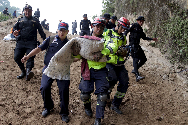 ATTENTION EDITORS - VISUAL COVERAGE OF SCENES OF INJURY OR DEATHA firefighter carries the body of a child retrieved from a mudslide in Santa Catarina Pinula, on the outskirts of Guatemala City, Oc ...