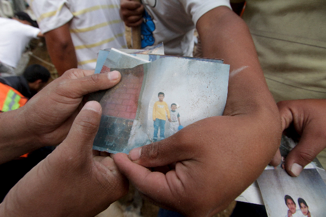 Residents show a photograph of two missing children at the site of a mudslide in Santa Catarina Pinula, on the outskirts of Guatemala City, October 2, 2015. The collapse of a hillside onto the tow ...