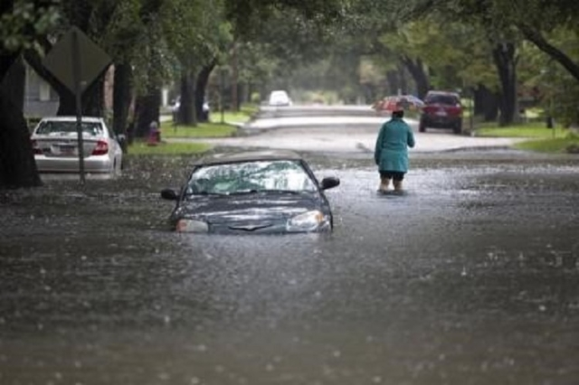 Clare Reigard of Georgetown, South Carolina, abandons her car after it stalled on Duke Street due to heavy rains in Georgetown, South Carolina October 4, 2015. (Reuters/Randall Hill)