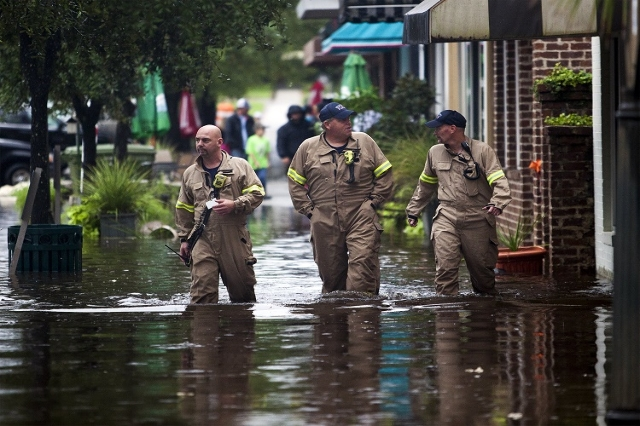 (L-R) Norman Beauregard, Kevin Attender and Chris Rogers of the Georgetown Fire Department, wade through flooded Front Street in Georgetown, South Carolina October 4, 2015. Most major roads throug ...