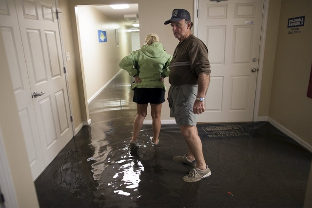 Chuck Richardson and his wife Ginger inspect their flooded Front Street office building in Georgetown, South Carolina October 4, 2015. (Reuters/Randall Hill)