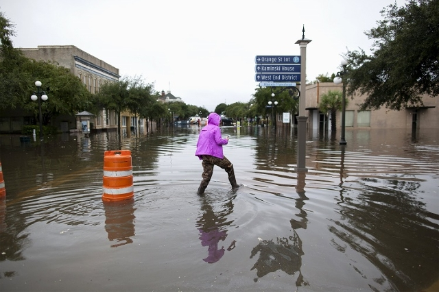 Mary Baldrick of Isle of Palms, South Carolina, wades through flooded Front Street in Georgetown, South Carolina October 4, 2015.  (Reuters/Randall Hill)