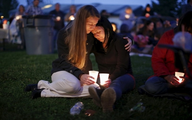 Heidi Wickersham (L), 31, comforts her sister Gwendoline Wickersham, 28, during a candlelight vigil for victims of the Umpqua Community College shooting in Winston, Oregon, United States, October  ...