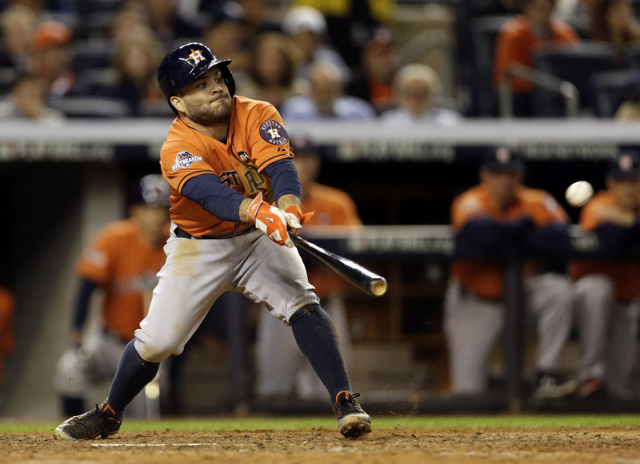 Oct 6, 2015; Bronx, NY, USA; Houston Astros second baseman Jose Altuve (27) hits an RBI single against the New York Yankees during the seventh inning in the American League Wild Card playoff baseb ...