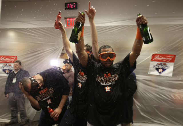 Oct 6, 2015; Bronx, NY, USA; Houston Astros third baseman Luis Valbuena (right) celebrates with teammates in the locker room after defeating the New York Yankees in the American League Wild Card p ...