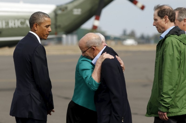 U.S. President Barack Obama watches as Eugene Mayor Kitty Piercy (2nd L) hugs Congressman Peter DeFazio (D-OR) upon arrival in Eugene, Oregon October 9, 2015. At right is Senator Ron Wyden (D-OR). ...