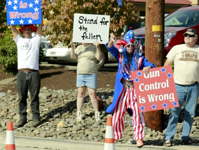 Pro-gun protesters hold signs as U.S. President Barack Obama's motorcade passes upon his arrival in Roseburg, Oregon October 9,  2015.  REUTERS/Kevin Lamarque