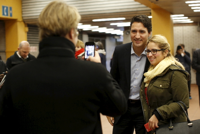 Liberal leader and prime minister-designate Justin Trudeau poses for a photo while greeting people at a subway station in Montreal, Quebec, October 20, 2015.  REUTERS/Chris Wattie