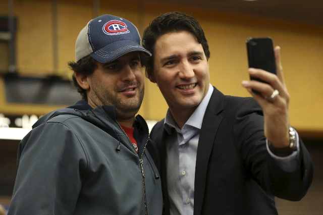 Liberal leader and prime minister-designate Justin Trudeau takes a selfie while greeting people at a subway station in his riding in Montreal, Quebec, October 20, 2015.  REUTERS/Chris Wattie