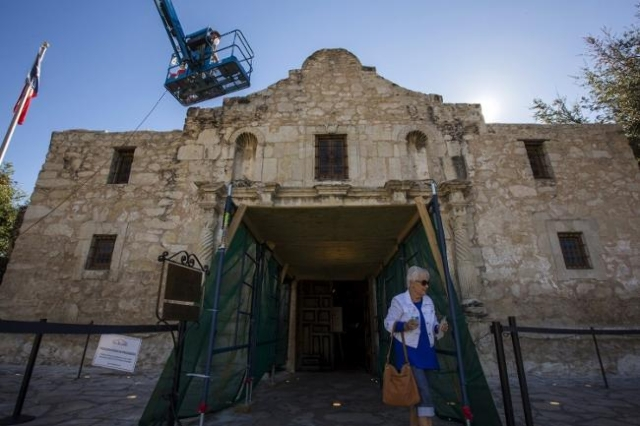 A woman walks past as men use a lift to repair and restore stonework along the curved facade of the Alamo in San Antonio, Texas October 26, 2015. (Reuters/Adrees Latif)