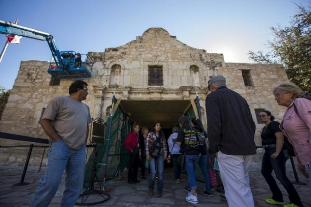 Visitors stand near the entrance as men use a lift to repair and restore stonework along the curved facade of the Alamo in San Antonio, Texas October 26, 2015. (Reuters/Adrees Latif)