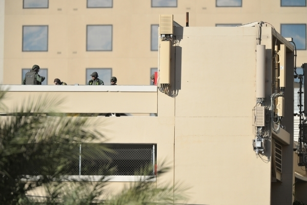 SWAT members gather on top of the Golden Nugget parking garage as a woman who escaped from the North Las Vegas Justice Court bailiffs while being transported stands on a railing outside of the sta ...