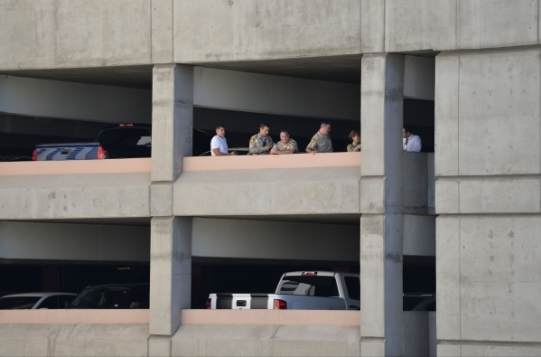 Police watch from an adjacent parking garage as a woman who escaped from the North Las Vegas Justice Court bailiffs while being transported stands on a railing outside of the stairwell on the top  ...