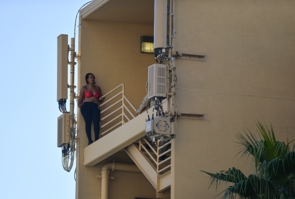 A woman who escaped from the North Las Vegas Justice Court bailiffs while being transported stands on a railing outside of the stairwell on the top level of the Golden Nugget parking garage as she ...