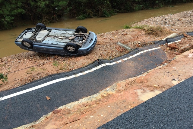 Road collapse in Lugoff, SC on October 5, 2015. The blue vehicle in the background is where the woman was rescued last night and the male DOT was recovered this morning. (Elise Miller/CNN)