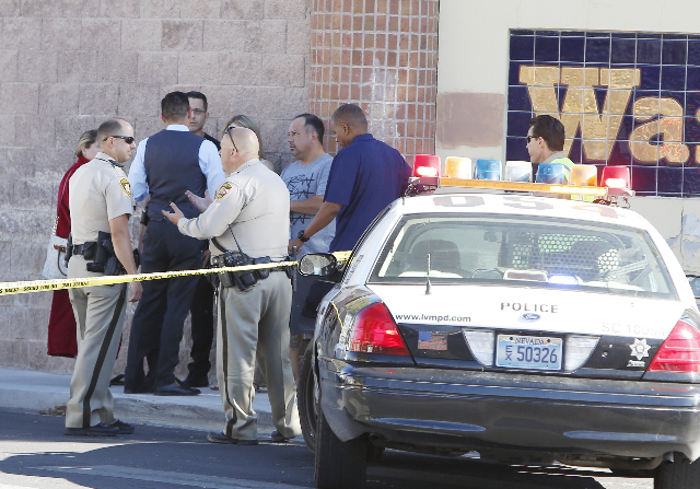 Las Vegas police are talking to evacuees as they investigate a barricade situation where three people are dead after a shooting in a southeast valley neighborhood Friday, Oct. 2, 2015 in the 7200  ...
