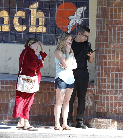Evacuees watch as Las Vegas police are investigating a barricade situation where three people are dead after a shooting in a southeast valley neighborhood Friday, Oct. 2, 2015 in the 7200 block of ...