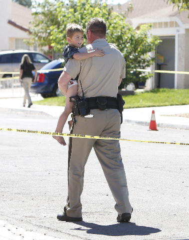 A Las Vegas police officer carries a boy to his house after the boy was evacuated from the neighborhood during a barricade situation where three people are dead after a shooting in a southeast val ...