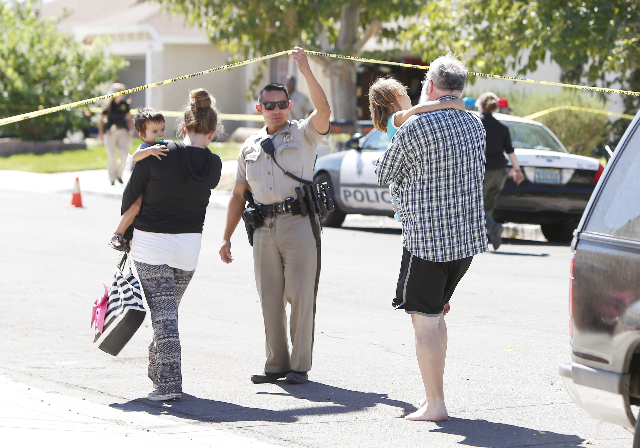 A Las Vegas police officer allows neighbors to return to their house after being evacuated during a barricade situation where three people are dead after a shooting in a southeast valley neighborh ...