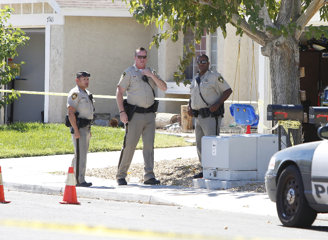 Las Vegas police officers stood guard infront of two houses after a barricade situation where three people were found dead after a shooting in a southeast valley neighborhood Friday, Oct. 2, 2015  ...