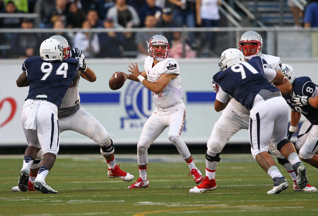 UNLV's Kurt Palandech (14) looks to throw a pass as UNR's Lenny Jones (94) and Kalei Meyer (91) close in during their football game at Mackay Stadium in Reno, Nev. on Saturday, Oct. 3, ...
