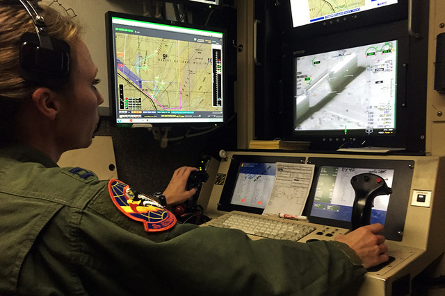 """Capt. Kristi controls an MQ-1B Predator remotely piloted aircraft during a training sortie inside a ground """"cockpit"""" Tuesday, June 16, 2015, at Creech Air Force Base at Indian Springs. T ..."""