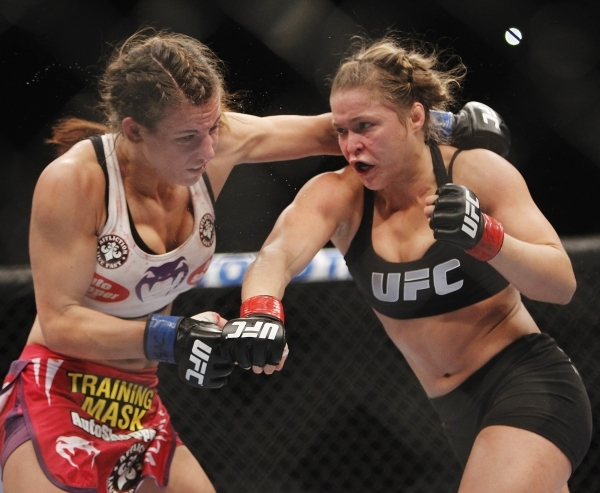 UFC women's bantamweight champion Ronda Rousey, right, trades blows with Miesha Tate during UFC 168 at the MGM Grand Garden on Dec. 28, 2013. Rousey won by third-round submission for her sec ...