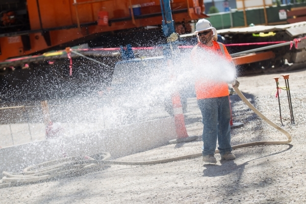 "A construction worker waters the ground before the ""topping off"" ceremony at the Lucky Dragon hotel-casino in Las Vegas on Friday, Sept. 11, 2015. Chase Stevens/Las Vegas Review-Journal  ..."