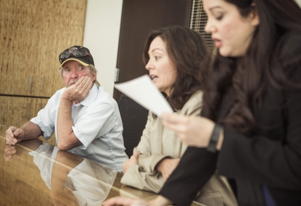 Wayne Fischer,left, listens while  attorneys Christine Miller, center, and Sophia Medina talks about how his finances were hurt by taking out a car-title loan during an interview at Legal Aid Cent ...