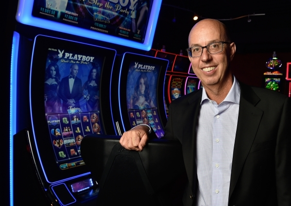 Scientific Games CEO Gavin Isaacs poses with a Playboy themed game at the company headquarters on Friday, Sept. 25, 2015, in Las Vegas. David Becker/Las Vegas Review-Journal