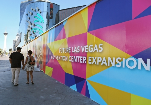 People walk by a colorful wall wrapped with advertisements for the Las Vegas Convention and Visitors Authority at the former Riviera hotel-casino Tuesday, Oct. 13, 2015, in Las Vegas. (Ronda Churc ...