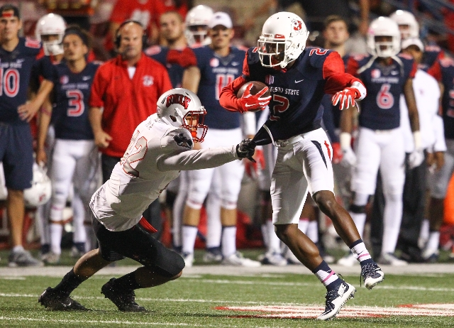 UNLV defensive back Peni Vea (42) grabs onto the shirt of Fresno State wide receiver Jamire Jordan (2) during a football game at Bulldog Stadium in Fresno, Calif. on Friday, Oct. 16, 2015. (Chase  ...