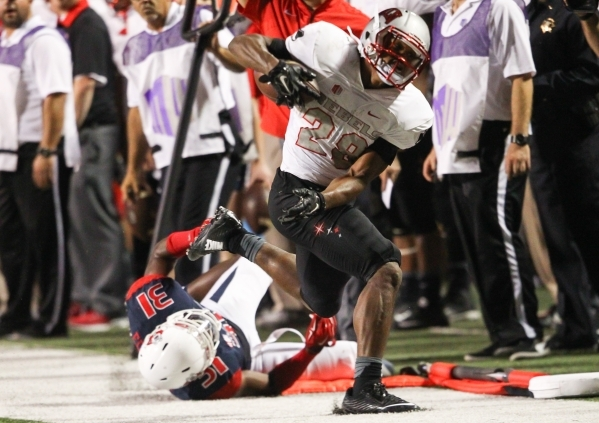 UNLV running back Keith Whitely (28) is taken out of bounds by Fresno State outside linebacker Ejiro Ederaine (31) during a football game at Bulldog Stadium in Fresno, Calif. on Friday, Oct. 16, 2 ...