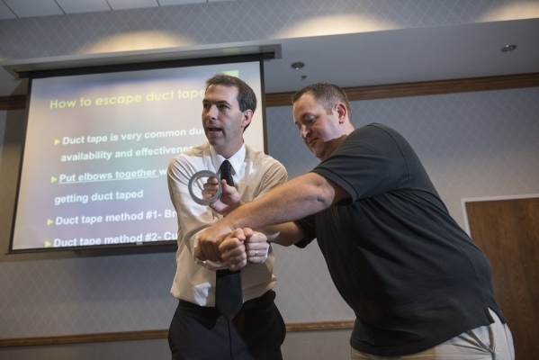 Former C.I.A. agent Jason Hanson, left, and his brother Brendan Hanson demonstrate how to escape duct tape during their Spy Escape & Evasion live training class at the Hampton Inn Tropicana in ...
