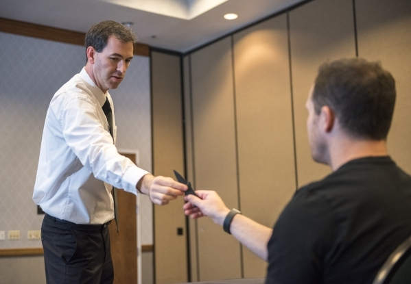 Former C.I.A. agent Jason Hanson, hands a credit card knife to an attendee during his Spy Escape & Evasion live training class at the Hampton Inn Tropicana in Las Vegas on Friday, Oct. 16, 201 ...