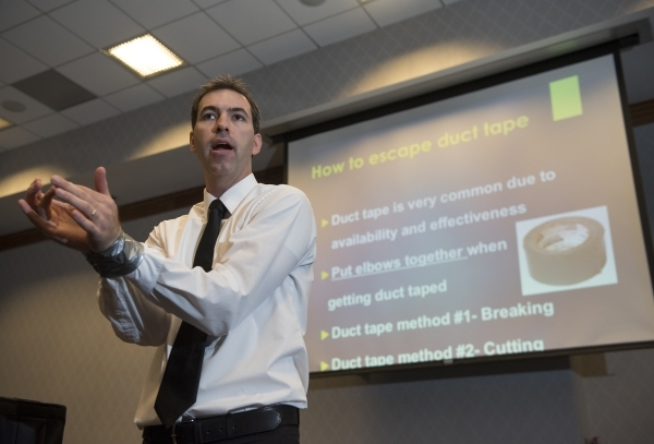 Former C.I.A. agent Jason Hanson demonstrates how to escape duct tape during his Spy Escape & Evasion live training class at the Hampton Inn Tropicana in Las Vegas on Friday, Oct. 16, 2015. Ma ...