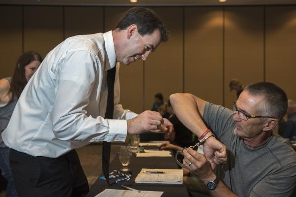 Former C.I.A. agent Jason Hanson, left, teaches attendee John Adamson how to escape handcuffs during his Spy Escape & Evasion live training class at the Hampton Inn Tropicana in Las Vegas on F ...