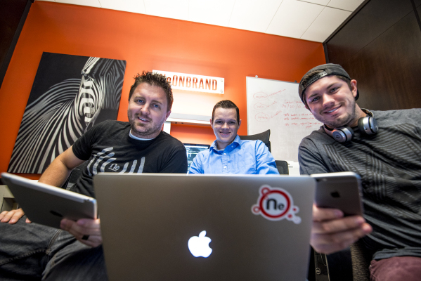 Kenny Eliason, from left, Spencer Guier, and Mychal Calderon pose for a photo while holding their Apple devices at the NeONBRAND office in Las Vegas on Wednesday, Oct. 28, 2015. Joshua Dahl/Las Ve ...