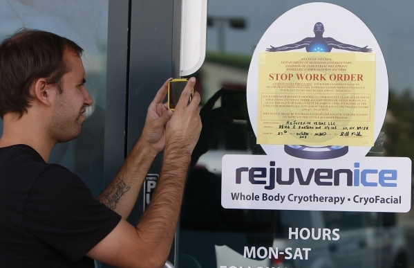 """An unidentified man takes a picture Tuesday, Oct. 27, 2015 of a """"Stop Work Order"""" sign that was posted on the front door of Rejuvenice where Chelsea Ake-Salvacion, 24, of Las Vegas worke ..."""