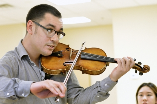 Conductor Yunior (cq) Lopez demonstrates how he wants a musical passage played during a Las Vegas Young Artists Orchestra rehearsal at 3661 S. Maryland Parkway in Las Vegas on Friday, Oct. 30, 201 ...